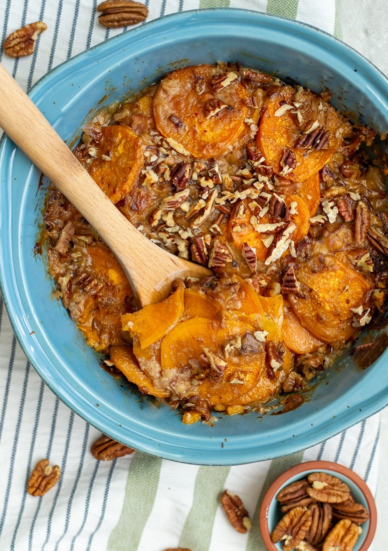 Scalloped sweet potatoes with creamy bacon sauce and topped with chopped pecans. This yummy fall side dish can easily be made paleo and whole30 as well. #sweetpotatoes #bacon #thanksgiving #pecans