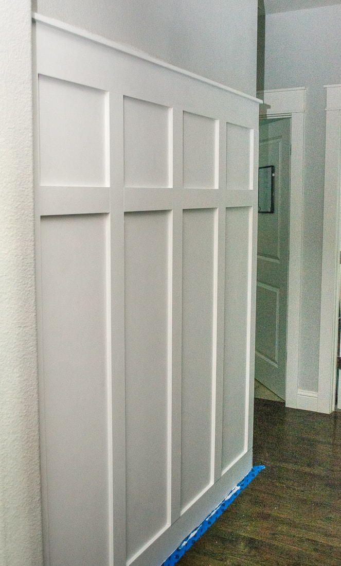 A step by step guide to installing a board and batten molding wall in a hallway with hooks to act as a mudroom. This DIY trim can add a little farmhouse decor to a boring space! #molding #diyproject