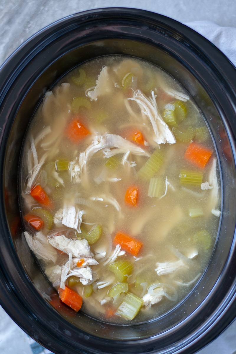 Crockpot chicken and rice soup is an easy set and forget homemade dinner that is heathy and delicious. Learn how to make it on the stovetop as well! #chickendinner #healthyreceipe