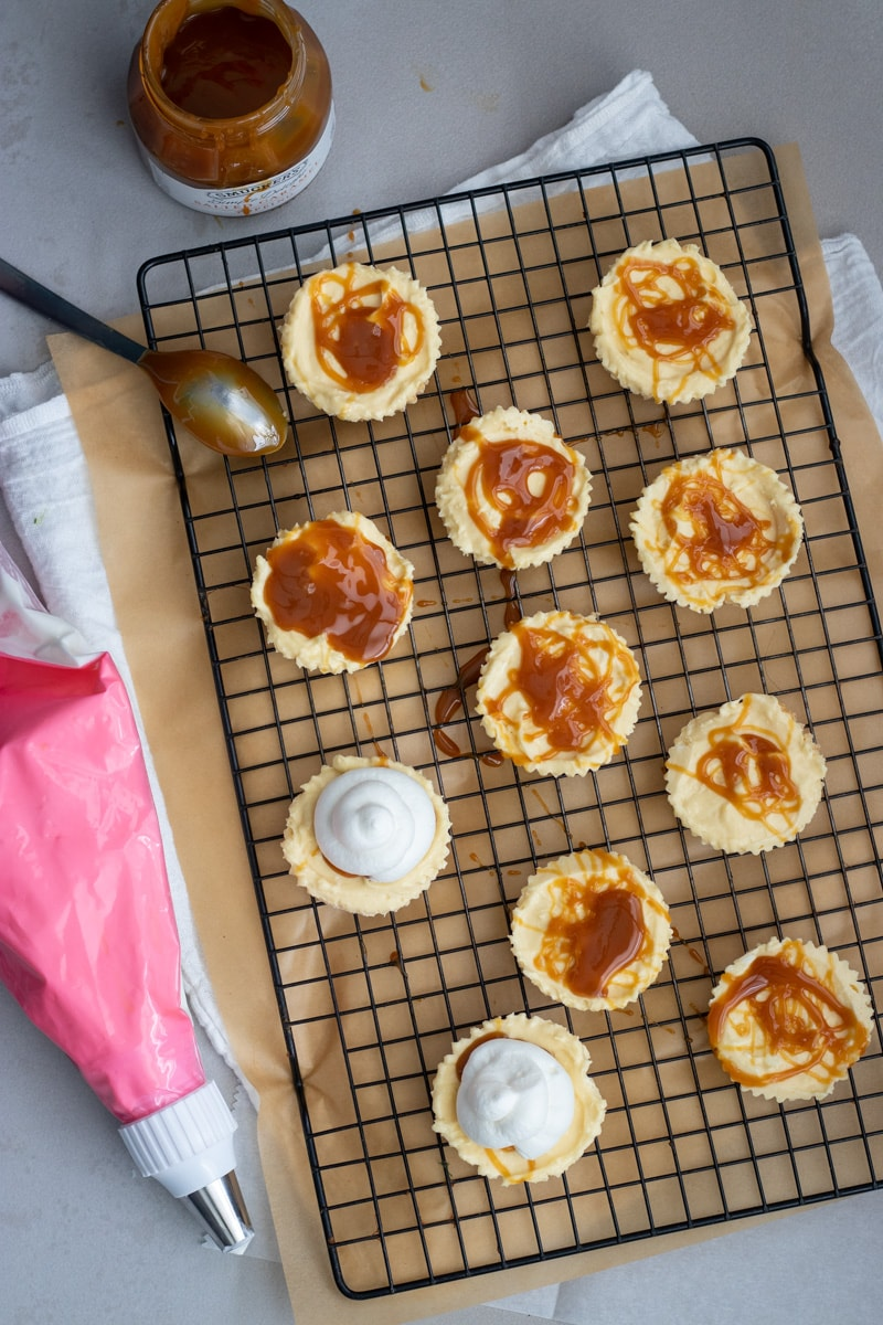 Mini banana pudding cheesecakes drizzled with salted caramel sauce.