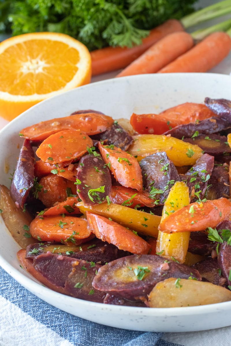 Rainbow carrots are roasted in butter or ghee with garlic and then drizzled with fresh squeezed orange juice and fresh parsley to make the perfect simple Easter side dish.