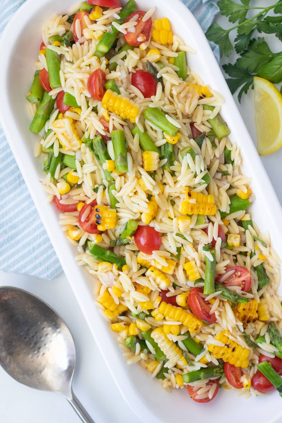 Summer orzo salad made with a quick lemon herb vinaigrette, cherry tomatoes, seared fresh corn, and asparagus.