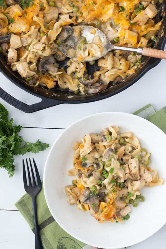 Healthy chicken noodle casserole with peas, mushrooms, chicken, and cheese.