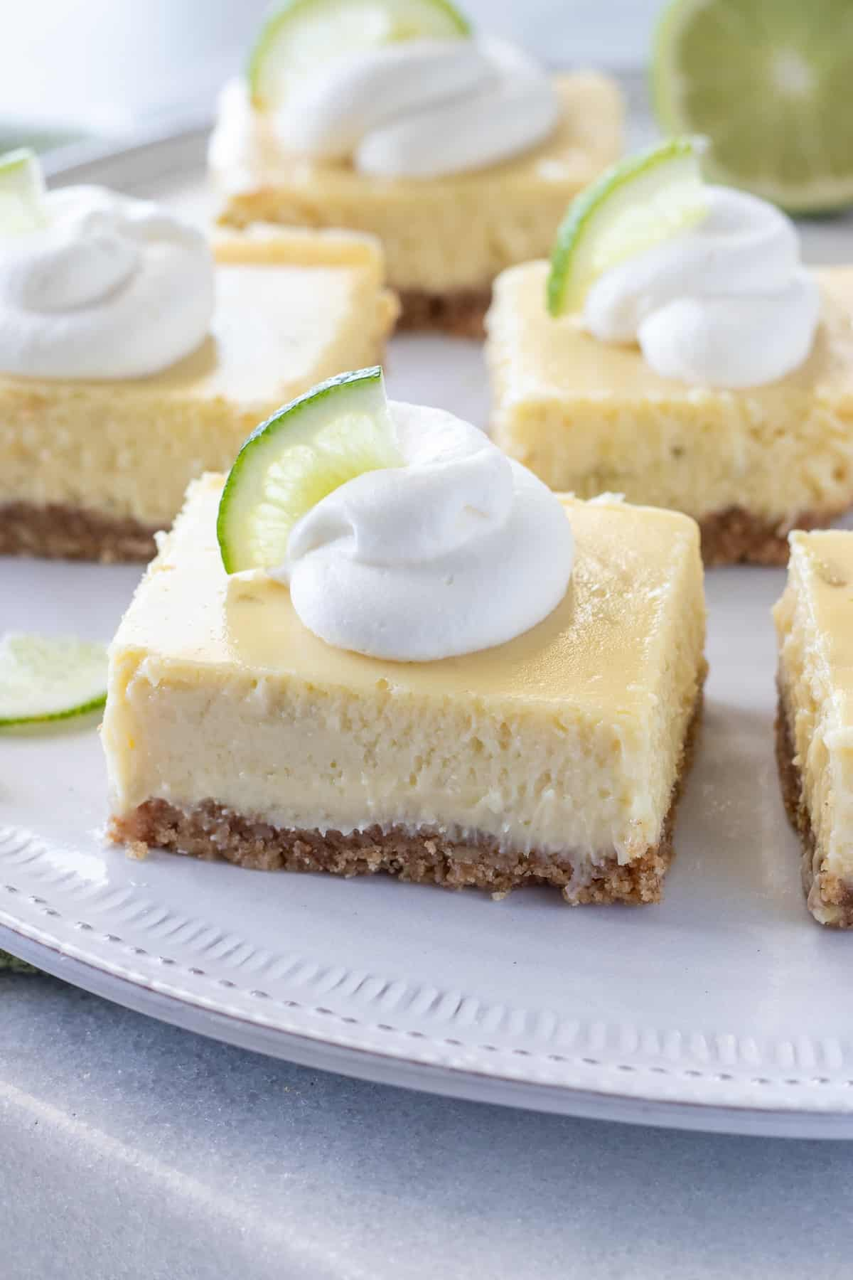 Key lime bars with a graham cracker crust topped with whipped cream